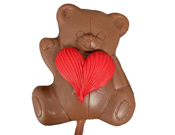 A milk chocolate Bear Pop holding a red icing Heart.